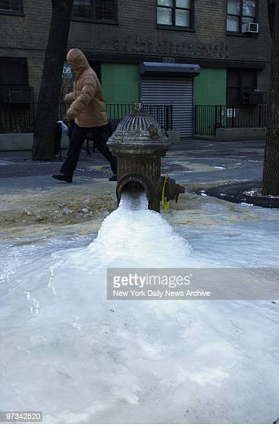 Pedestrian bundled up against the cold hurries by a fire hydrant spouting ice on E 27th St as New Yorkers struggle through the 11th straight day of...