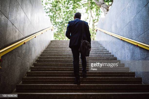 pedestrian businessman walking out of metro - steps stock photos and pictures