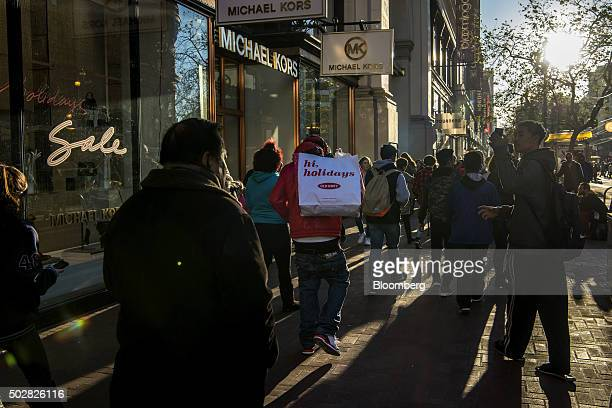 A pedestrian caries a shopping bag through downtown San Francisco California US on Monday Dec 28 2015 A late surge in shopping and pentup demand for...