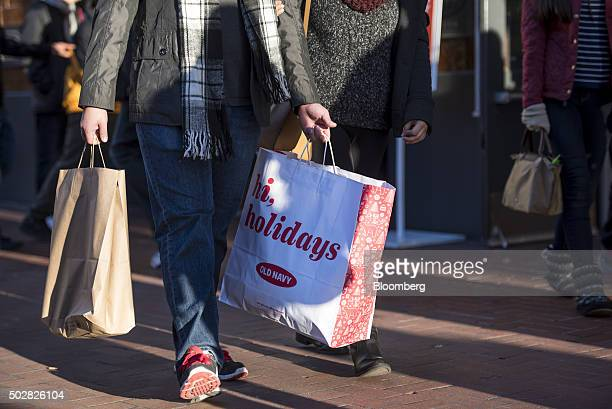 A pedestrian caries shopping bags through downtown San Francisco California US on Monday Dec 28 2015 A late surge in shopping and pentup demand for...