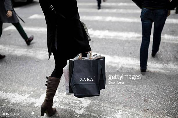 A pedestrian carries a bag along a street after shopping in a Zara fashion store operated by Inditex SA in central Thessaloniki Greece on Monday...