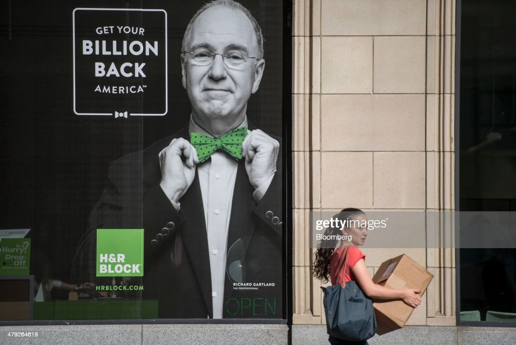 A pedestrian carries a box as she walks past an H&R Block, Inc. office in San Francisco, California, U.S., on Friday, March 14, 2014. The deadline for filing 2013 U.S. taxes is April 15. Photographer: David Paul Morris/Bloomberg via Getty Images