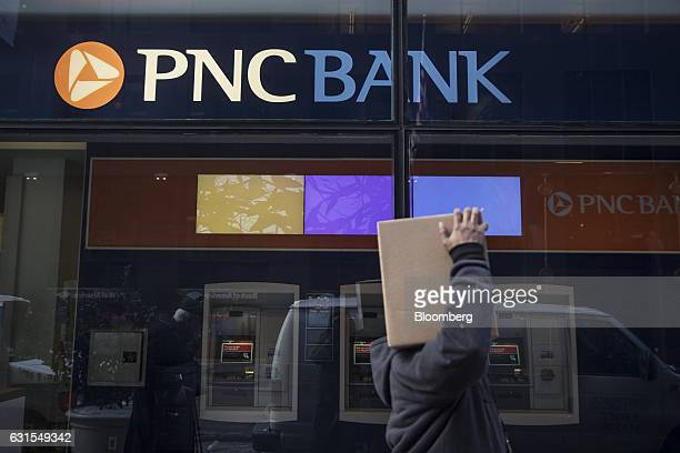 A pedestrian carries a box while passing in front of PNC Financial Services Group Inc bank branch in New York US on Monday Jan 9 2017 PNC Financial...