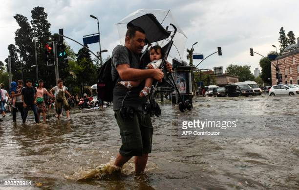 A pedestrian carries a child in a pushchair as he crosses a street after a heavy downpour of rain and hail at Besiktas near Istanbul on July 27 2017...