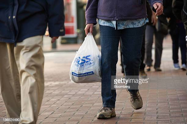 Pedestrian carries a Ross Stores Inc. Shopping bag in San Francisco, California, U.S., on Thursday, Jan. 5, 2012. Retailers are starting to pay the...