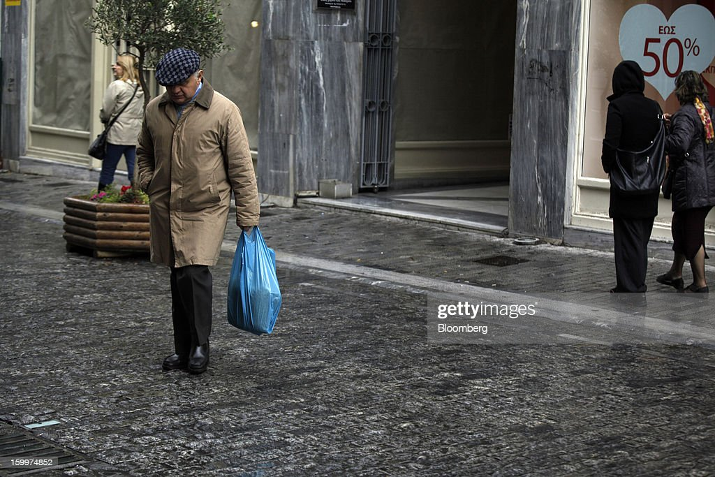 A pedestrian carries a shopping bag across a street in Athens, Greece, on Thursday, Jan. 24, 2013. Greece's government has implemented budget cuts and economic reforms to tame a fiscal deficit that has led to bailouts from the European Union and the International Monetary Fund. Photographer: Kostas Tsironis/Bloomberg via Getty Images
