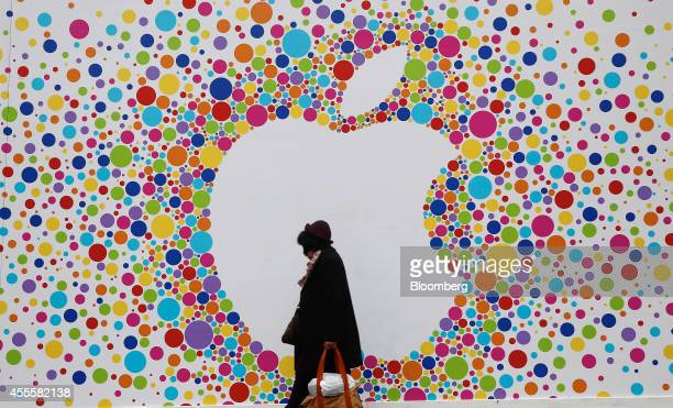 A pedestrian carries a shopping bag as she passes a giant Apple Inc logo outside a new Apple store still under development on Princess Street in...