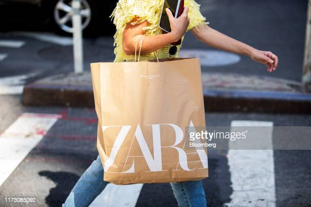 A pedestrian carries a shopping bag from a Zara fashion store operated by Industria de Diseno Textil SA while walking along a street in New York US...
