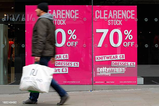 A pedestrian carries a shopping bag past a window advertisement for a stock clearance sale at a Select store in Manchester UK on Monday April 1 2013...