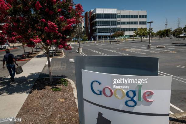 Pedestrian carries a shopping bag past an empty parking lot at the Google campus in Mountain View, California, U.S., on Monday, July 27, 2020....
