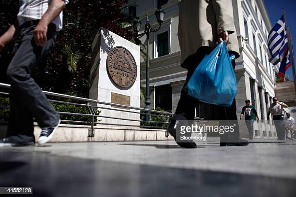 A pedestrian carries a shopping bag past an old one drachma coin sculpture outside the town hall in Athens Greece on Wednesday May 16 2012 Greek...