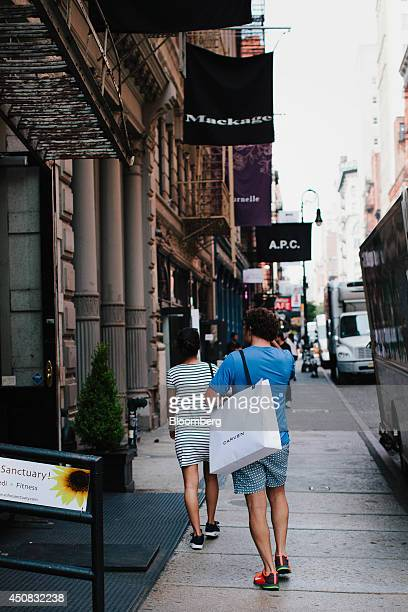 A pedestrian carries a shopping bag while walking in the SoHo neighborhood of New York US on Wednesday June 18 2014 The Bloomberg Consumer Comfort...