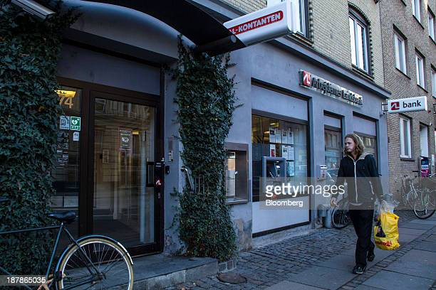 Pedestrian carries a yellow shopping bag as he walks past a Arbejdernes Landsbank bank branch in Copenhagen, Denmark, on Tuesday, Nov. 12, 2013....