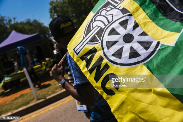 A pedestrian carries an ANC flag during the 54th national conference of the African National Congress party in Johannesburg South Africa on Sunday...
