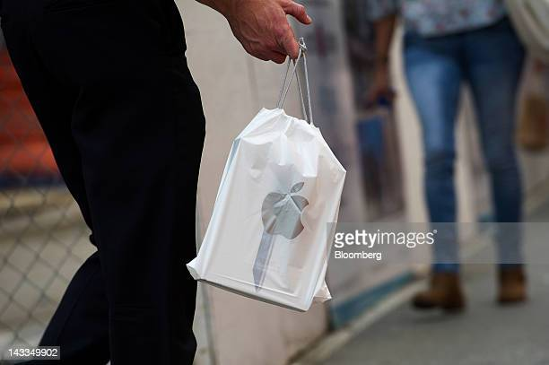A pedestrian carries an Apple Inc shopping bag in San Francisco California US on Tuesday April 24 2012 Apple Inc profit almost doubled last quarter...