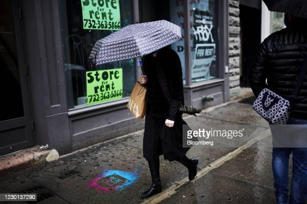 Pedestrian carries an umbrella and Zara shopping bag while walking in the SoHo neighborhood of New York, U.S., on Monday, Dec. 14, 2020. The U.S....