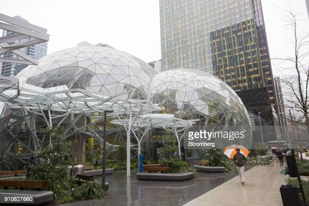 A pedestrian carries an umbrella while passing in front of the Amazoncom Inc Spheres in Seattle Washington US on Tuesday Jan 23 2018 The online...