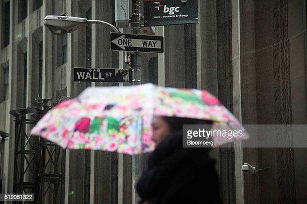 A pedestrian carries an umbrella while walking along Wall Street near the New York Stock Exchange in New York US on Wednesday Feb 24 2016 US stocks...