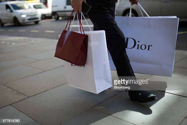 A pedestrian carries Dior branded shopping bags after leaving a Christian Dior SA luxury store on New Bond Street in London UK on Tuesday July 19...