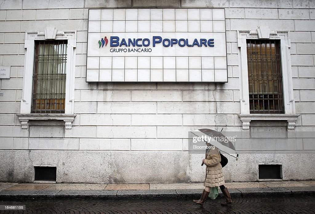 A pedestrian carries her shopping in a plastic carrier bag as she passes the headquarters of Banco Popolare SC in Verona, Italy, on Monday, March 25, 2013. Italy's economy remains mired in its longest recession in two decades and a month-old political impasse threatens to increase sovereign-debt yields and bank funding costs. Photographer Alessia Pierdomenico/Bloomberg via Getty Images
