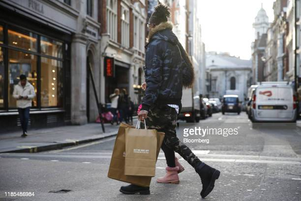 A Pedestrian carries Nike Inc branded brown paper shopping bags on Oxford Street in London UK on Friday Nov 29 2019 UK consumer confidence remained...
