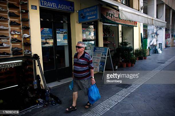A pedestrian carries shopping bags along a street past a travel agent store in Athens Greece on Friday Aug 9 2013 Greece's economy contracted for a...