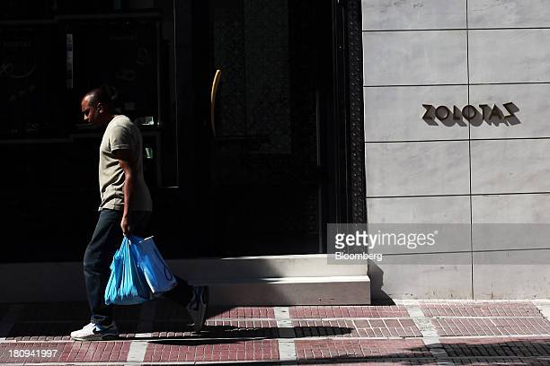 A pedestrian carries shopping bags along an empty street ahead of a demonstration to mark the start of a 48hour strike by Greece's biggest...