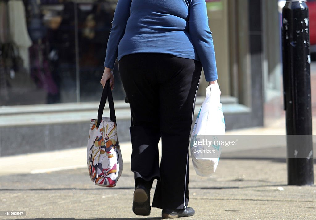 A pedestrian carries shopping bags as she passes stores in Eastbourne, U.K., on Tuesday, April 1, 2014. Pensioners and savers have seen returns on their money shrink since the financial crisis drove interest rates to a record low. Photographer: Chris Ratcliffe/Bloomberg via Getty Images
