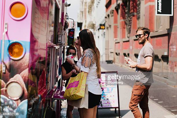 A pedestrian carries shopping bags while getting ice cream from a truck in the SoHo neighborhood of New York US on Wednesday June 18 2014 The...