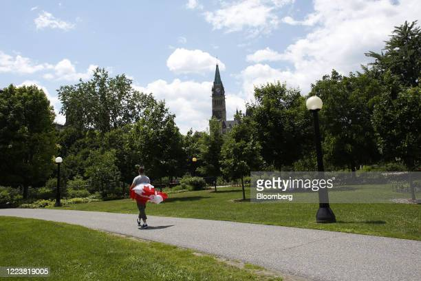 Pedestrian carrying a Canadian flag walks through a nearly empty Majors Hill Park on Canada Day in Ottawa, Ontario, Canada, on Wednesday, July 1,...