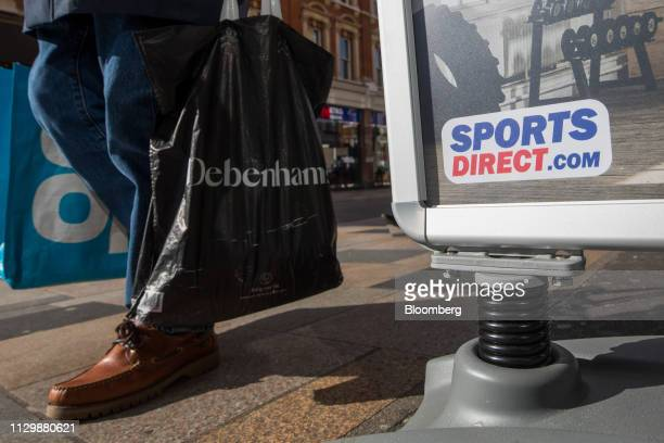 A pedestrian carrying a Debenhams Plc carrier bag passes an advertisement for a Sports Direct International Plc concession in London UK on Monday...