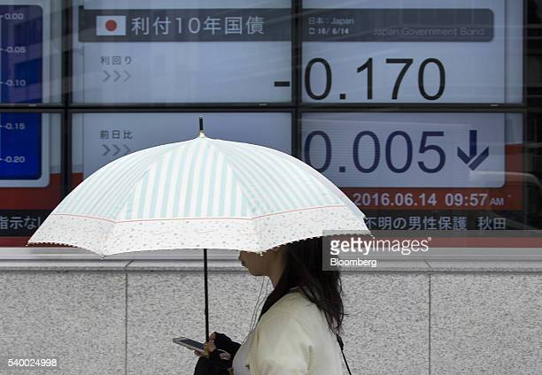 A pedestrian carrying an umbrella walks past an electronic stock board displaying the yield for 10year government bond outside a securities firm in...