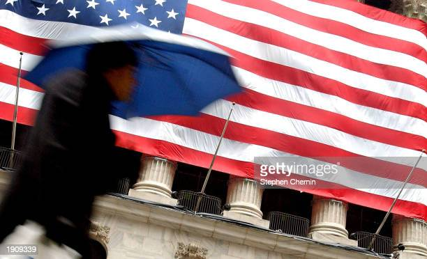 A pedestrian carrying an umbrella walks past the New York Stock Exchange April 9 2003 in New York City Rain continued for a second day after New York...