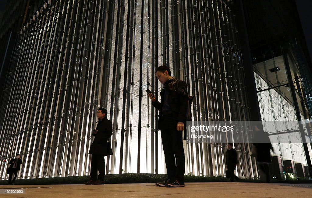 A pedestrian, center, right, looks at his smartphone while standing front of the Mizuho Financial Group Inc. headquarters in Tokyo, Japan, on Thursday, Jan. 29, 2015. Mizuho Financial Group, Japan's third largest bank, is scheduled to report third-quarter earnings on Jan. 30. Photographer: Tomohiro Ohsumi/Bloomberg via Getty Images