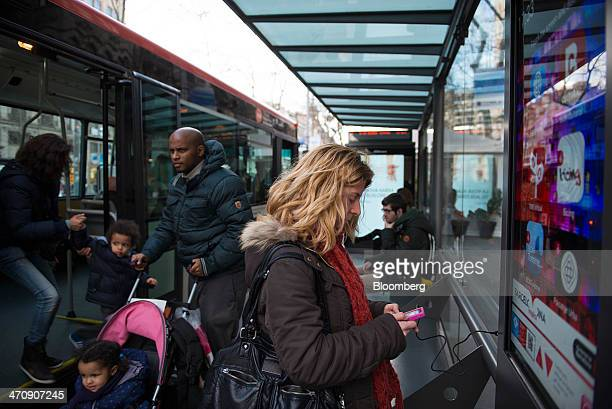 A pedestrian charges her mobile phone at a smart bus stop in Barcelona Spain on Thursday Feb 20 2014 A smart city initiative which also involves...