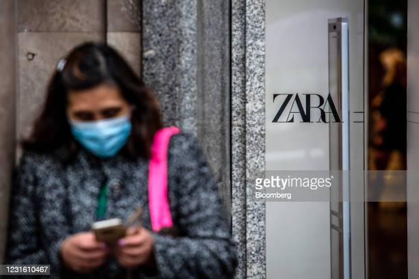 Pedestrian checks a mobile phone outside a Zara clothing store, operated by Inditex SA, in Barcelona, Spain, on Monday, March 8, 2021. Inditex will...