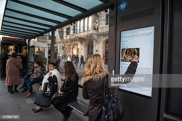 A pedestrian checks city visitor information on an interactive digital screen at a smart bus stop in Barcelona Spain on Thursday Feb 20 2014 A smart...