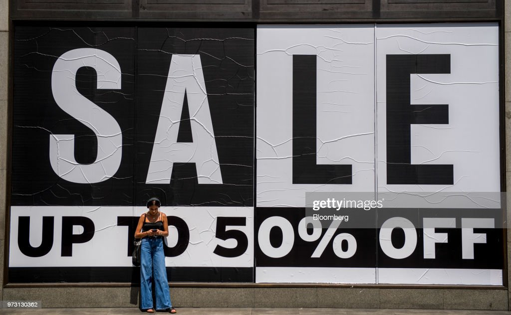 A pedestrian checks her mobile phone in front of a large sale sign offering up to 50 percent off outside Topshop, operated by Arcadia Group Ltd., on Oxford Street in central London, U.K., on Wednesday, June 13, 2018. U.K. department-store chain House of Fraser said it plans to shut more than half its outlets, putting 6,000 jobs at risk. Photographer: Chris J. Ratcliffe/Bloomberg via Getty Images