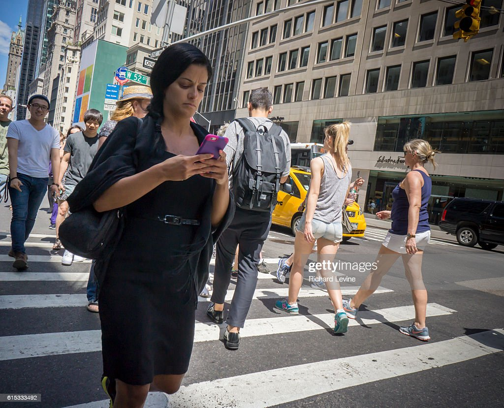 A pedestrian checks her smartphone while crossing a Fifth Avenue intersection in New York on Thursday, July 23, 2015. A bill introduced in New Jersey would make it illegal for anyone to text and walk at the same time. Offenders could be fined $50 and/or 15 days in jail. No date has been set for when this bill will be voted on.