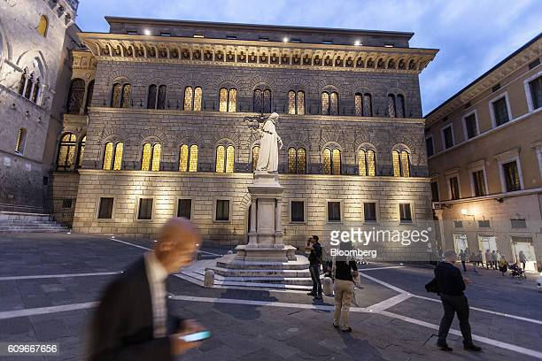 A pedestrian checks his smartphone device in Piazza Salimbeni as the statue of Sallustio Bandini an economist and politician stands in front of Monte...