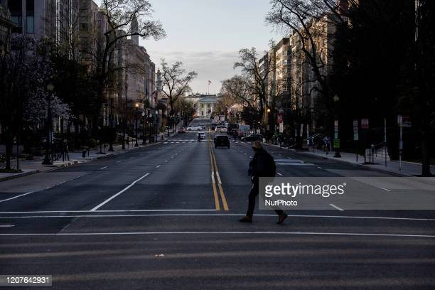 A pedestrian cross 16th street in Washington DC during what would normally be the morning rush after most businesses have required employees to work...