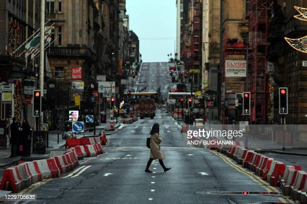 Pedestrian crosses a near-deserted St. Vincent Street in central Glasgow, on November 21 following the introduction of further coronavirus...