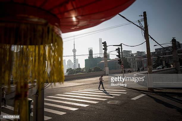 A pedestrian crosses a road as buildings of Pudong's Lujiazui financial district stand in the distance in Shanghai China on Friday Oct 2 2015 China's...