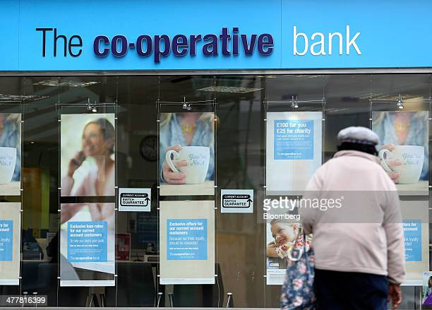 A pedestrian crosses a road near a CoOperative Bank Plc bank branch in Luton UK on Tuesday March 11 2014 CoOperative Group Ltd Chief Executive...