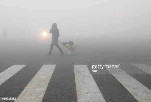 TOPSHOT A pedestrian crosses a smogshrouded street in Lianyungang eastern China's Jiangsu province on December 19 2016 Hospital visits spiked roads...