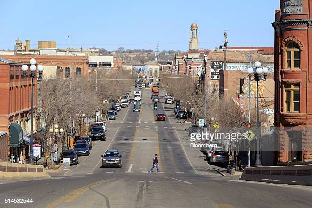A pedestrian crosses a street in downtown Pueblo Colorado US on Thursday Feb 25 2016 About 938 dispensaries which outnumber Starbucks in Colorado in...