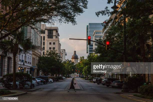 Pedestrian crosses a street in front of the South Carolina State House in Columbia, South Carolina, U.S., on Wednesday, July 15, 2020. At least...
