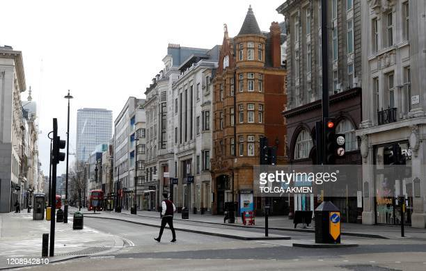 Pedestrian, crosses an empty road on a deserted Oxford Street in London on April 2 as life in Britain continues during the nationwide lockdown to...