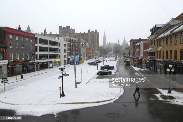 A pedestrian crosses an empty street during morning rush hour March 23 2020 in Ottawa Canada