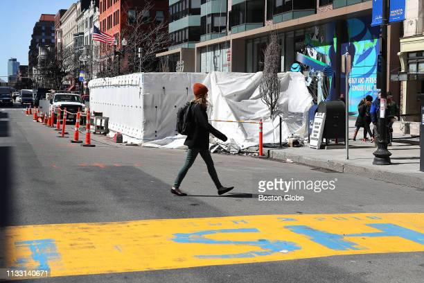 A pedestrian crosses Boylston Street at the Boston Marathon finish line past a tarp covering the work being done on a memorial to the victims of the...